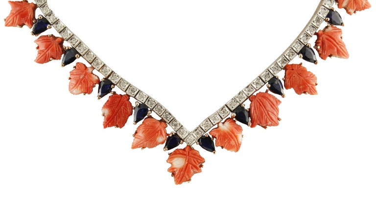 Beautiful choker necklace in 9kt rose gold and silver, all studded with diamonds from ct 1.81, with beautiful coral leaves from 4.30 g alternating with very bright sapphires from ct 4.74. Total weight g 35. Sapphires ct 4.74 Diamonds ct 1.81 Coral g