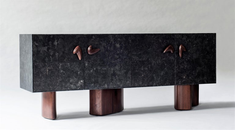 Inspired by the graphic motifs of Le Corbusier's mural paintings, the solid form of the Corbu cabinet is defined by rhythmically placed handles. Architectural legs lend support and an unexpected element of asymmetry. The cabinet body is sheathed in