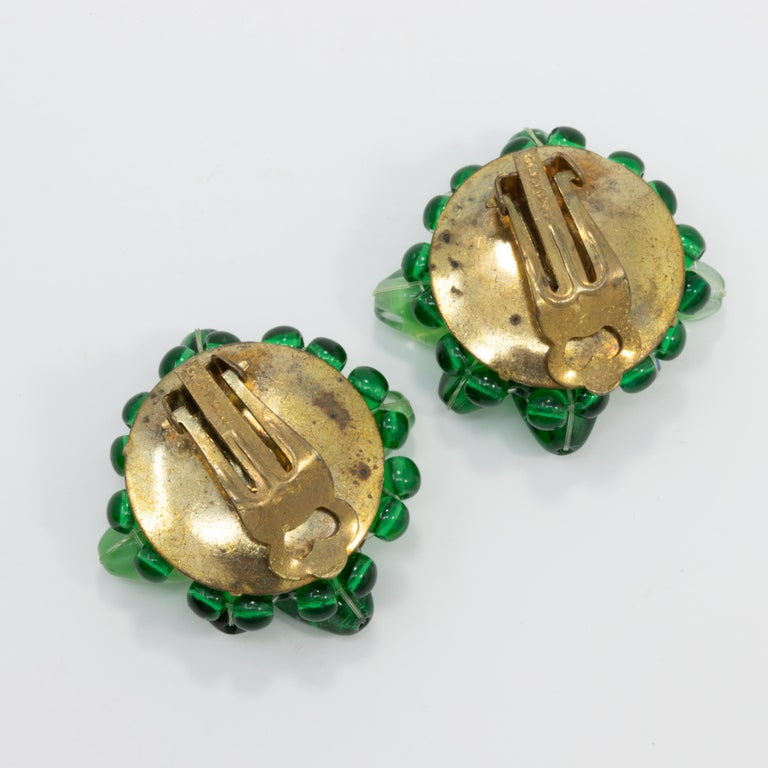 Pair of vintage clip on Coro earrings, each featuring emerald and peridot crystals and a single green faux pearl. Comes with original paper label, marked