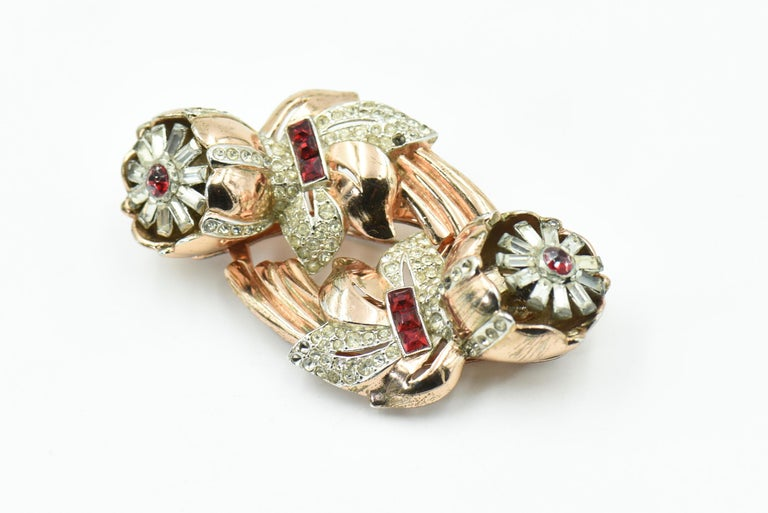 An exquisite example of Coro's Camellia quivering (trembler) duette clips brooch. This brooch is a rare edition which is plated in rose (pink) gold.  The trembling flowers have red crystal centers with clear petals. The leaves are clear crystals