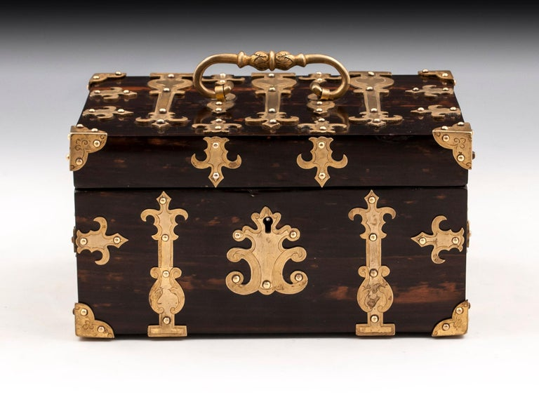 Antique Coromandel trinket box with ornate engraved applied brass mounts, corner brackets, carry handle and escutcheon.   The interior is lined in vibrant marble effect paper with a cushioned velvet pad for the base.   This antique trinket box
