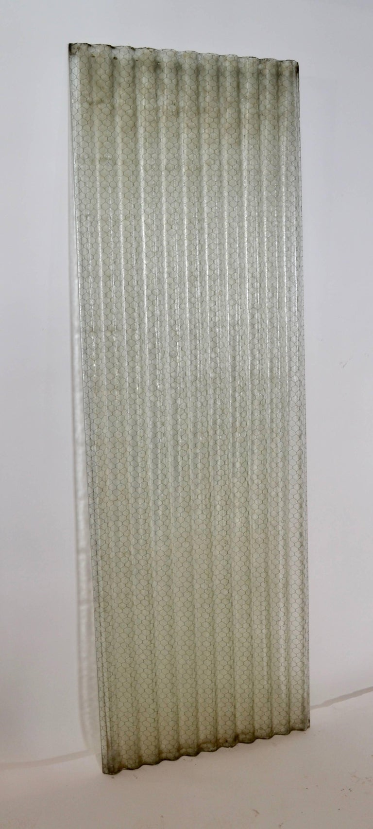 These corrugated chicken wire glass panels were harvested from a former US Naval facility. The panels were used in vertical applications and offered both security as well as safety. Some have edge chipping that is consistent with age and use. The