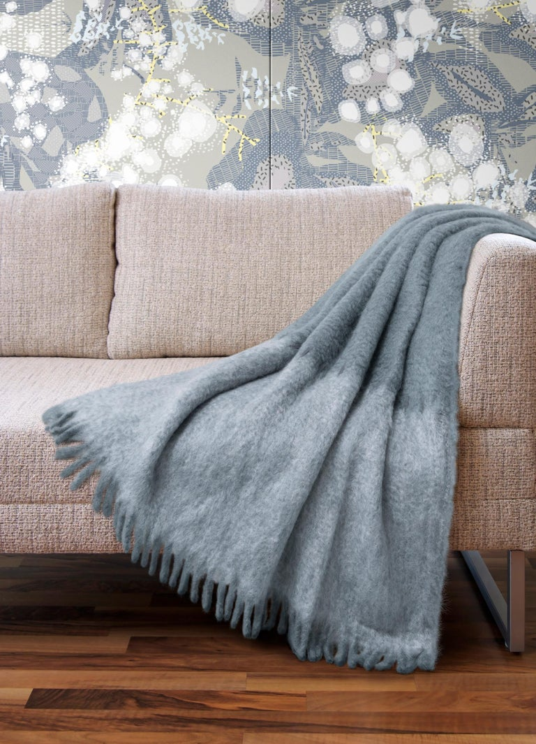 Discreet yet with character, the Cortina Mohair plaid ensures a soft final touch to any environment. Its elegance comes from the gentle fringes and contrasting ice grey and darker grey tonalities, underlined by a fine diagonal stitching. The natural