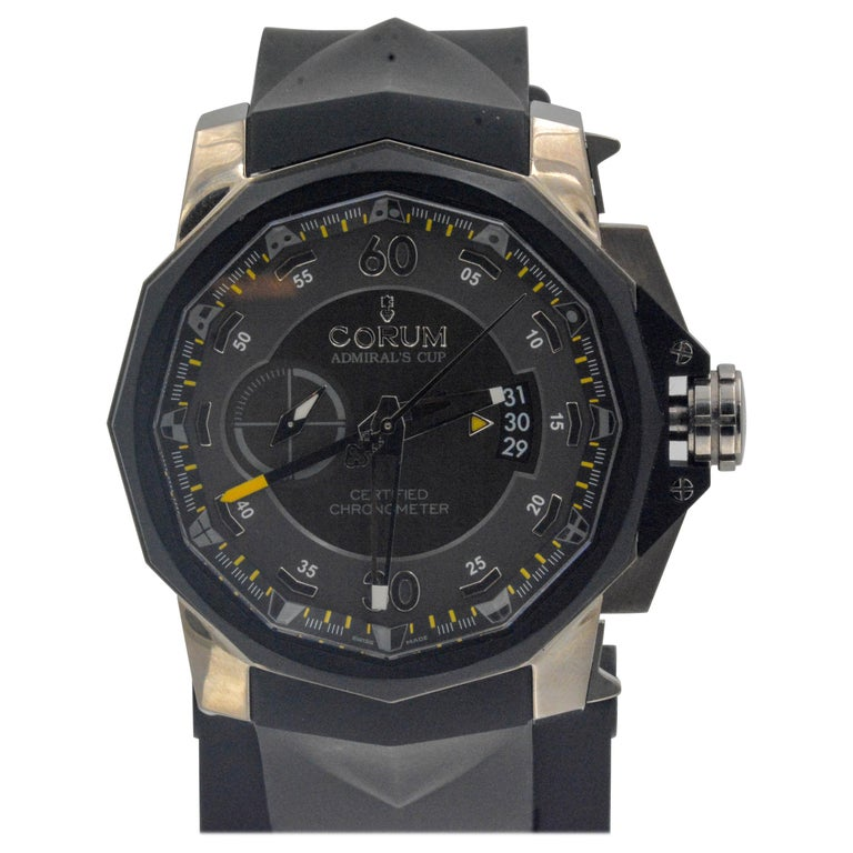 • Model: Corum Admirals Cup Chronograph • Movement: Automatic  • Case Size: 48mm  • Case Material: Stainless Steel, back see- through sapphire crystal • Dial: Grey/black dial, sub dials, date wheel • Strap: Black rubber strap  • Closure/Clasp Type: