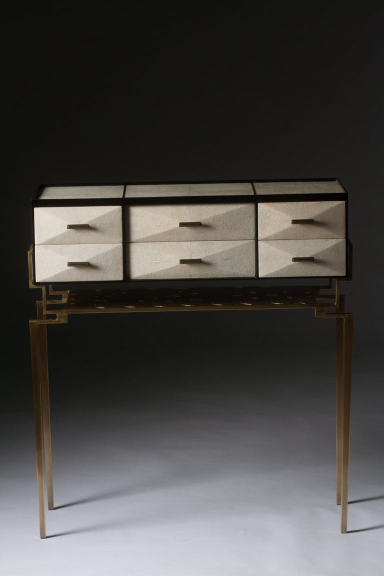 The Cosima 7 console, is both practical and stunning in design. This smaller console includes 6 beveled geometric drawers that can used to store anything from jewelry to stationary. This piece includes a bronze-patina brass shelf below the drawers