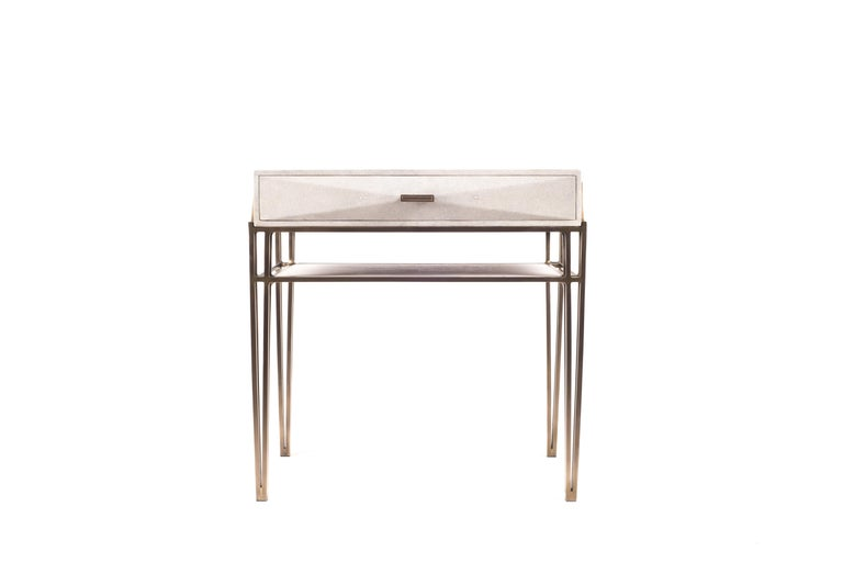 The Cosima bedside table, is both practical and stunning in design. This bedside table is the perfect accent piece for any intimate space. This table has one large drawer, and the top piece in cream shagreen can be removed from the bronze-patina