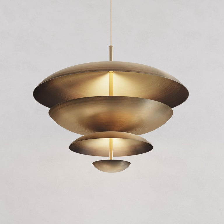 Finely hand-spun brass plates make up this pendant light, finished in a mixed patina. One side is dark end colour bronze and the other a gently brushed brass gradient. The light is projected into the shade and reflects out, illuminating without