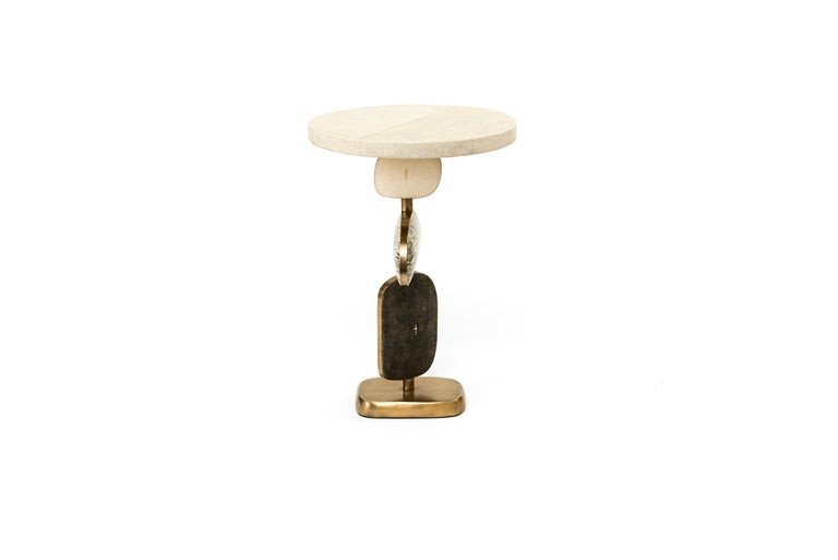 The Cosmo side table by Kifu Paris is a whimsical and sculptural piece, inlaid in reversible cream shagreen/ black shagreen, Baguio stone, black pen shell and bronze-patina brass. The amorphous shapes on the bottom part can be moved to adjust the