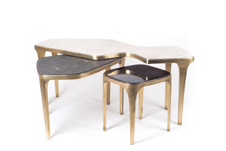 The Cosmos nesting coffee table small is both Minimalist and dramatic. The top is inlaid in black pen shell, that is hand-selected by artisans, and completed with bronze-patina brass. With its beautiful amorphous shape this piece adds a statement to