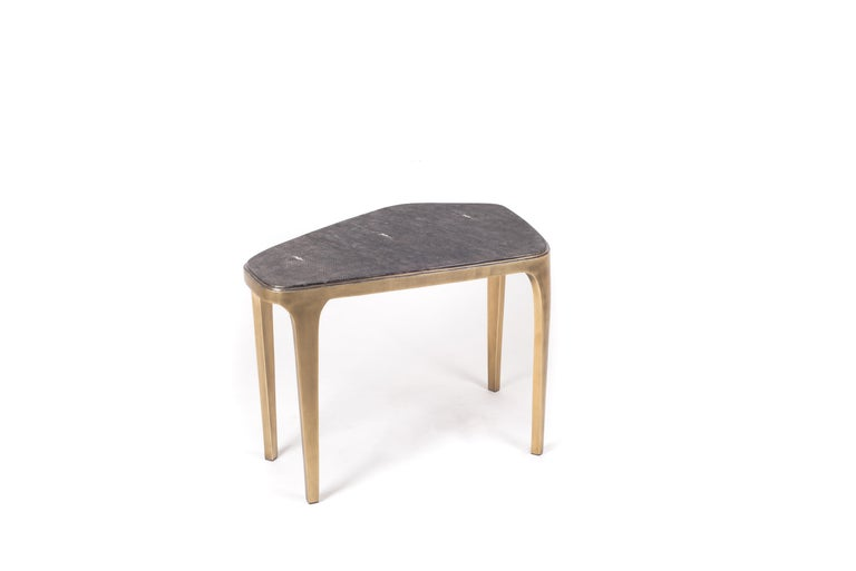 The Cosmos nesting coffee table medium is both Minimalist and dramatic. The top is inlaid in black shagreen, that is hand-dyed by artisans, and completed with bronze-patina brass. The designer calls this finish