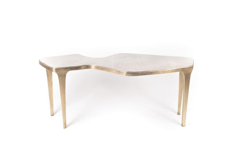 The cosmos nesting coffee table large is both Minimalist and dramatic. The top is inlaid in cream shagreen, that is hand-dyed by artisans, and completed with bronze-patina brass. The designer calls this finish