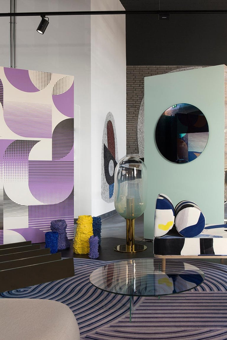 A large mirror reflecting through various swatches of color. The mirror offers a wide range of colours from light to dark swerve. The mirror is organised in an even concentric block pattern. The reflection of the mirror makes each color multiply