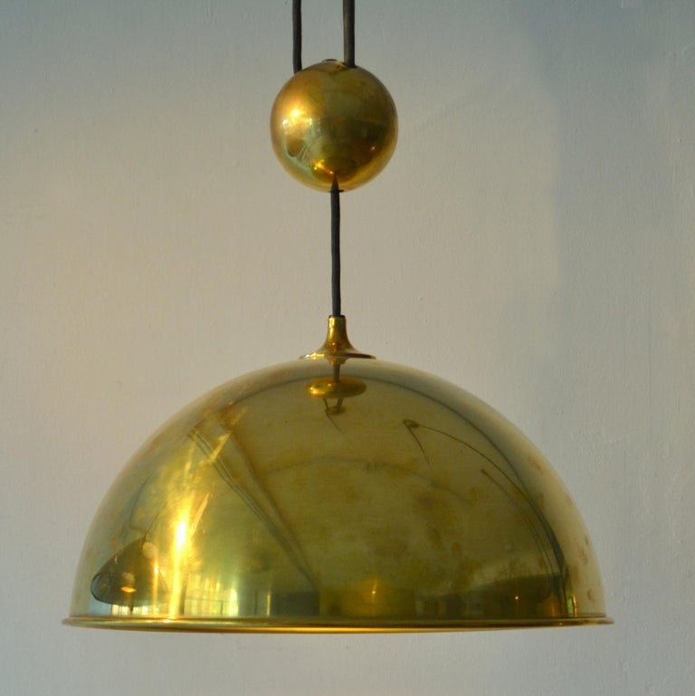 Counterbalance pendant 'Posa' by Florian Schulz with centre weight. Strong and minimal pendant in a high quality spun brass moves smoothly up and down due to the solid brass counterweight. The brass is coated.  Excellent timeless design of a very