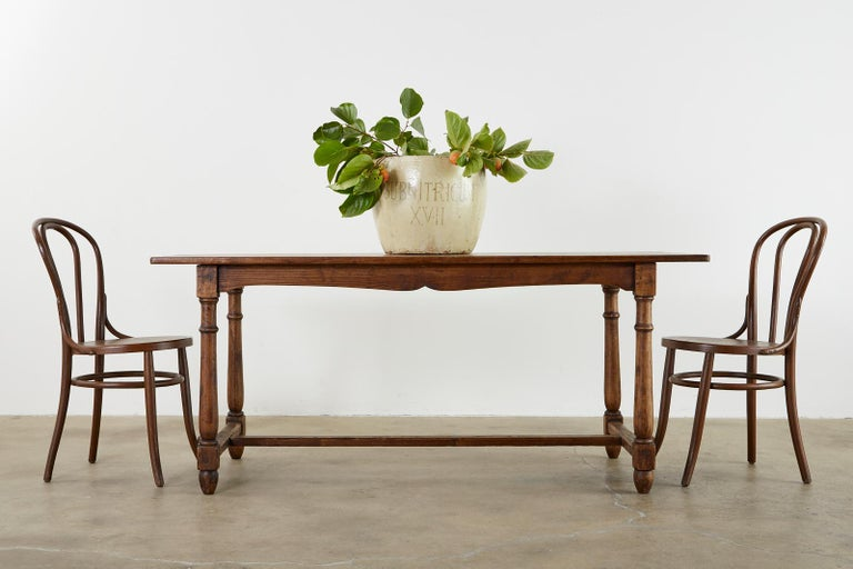 Rustic Country English Provincial style farmhouse dining table. handcrafted from oak having a plank top and an exposed mortise and Tenon joinery trestle base. The table apron has scalloped sides and is supported by turned round legs ending with