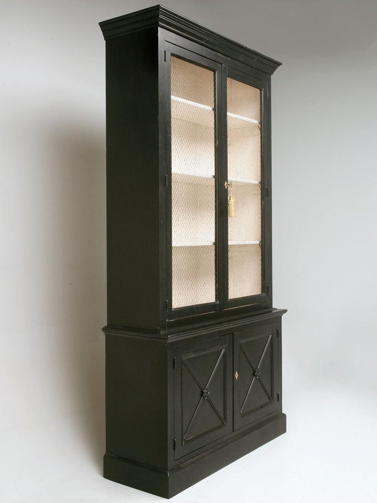 Custom Country French inspired handmade 4-door bookcase in the Directoire style, finished with a black brushed painted exterior, French vanilla interior and European style chicken wire in the upper doors. Crafted by hand here in our very own Chicago