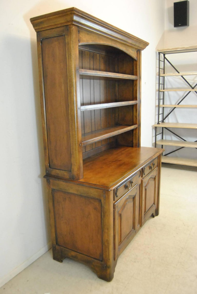 A beautiful country French open cupboard by Ralph Lauren. This charming piece features dovetailed drawers, distressed solid cherry, heavy cast brass hardware, raised panel doors and an adjustable lower shelf. This comes in two pieces. The dimensions