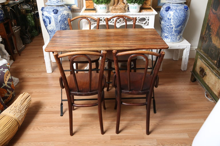 French wood slat folding Campaign table along with four companion chairs.