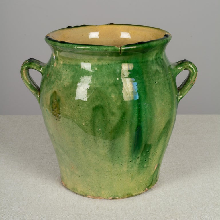 An earthenware confit pot from the Southwest of France with traditional green glaze. These ordinary earthenware vessels were once used daily in the French country home and have beautiful rustic glazes of green, ochre and terracotta. Nice decorative