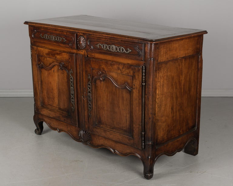 An early 19th century Louis XV style French buffet from the Loire Valley made of solid apple wood. Beautiful character to the wood and simple hand-carvings including a scalloped apron with large shell motif. Interior provides ample storage, opening