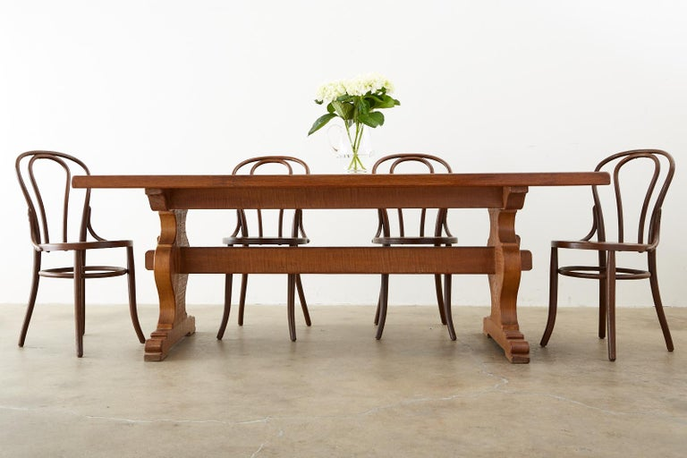 Rustic country French farmhouse trestle dining table constructed from oak. The table features a 2 inch thick solid oak top supported by beautifully shaped trestle legs ending with shoe feet. The legs are conjoined by a stretcher having an exposed