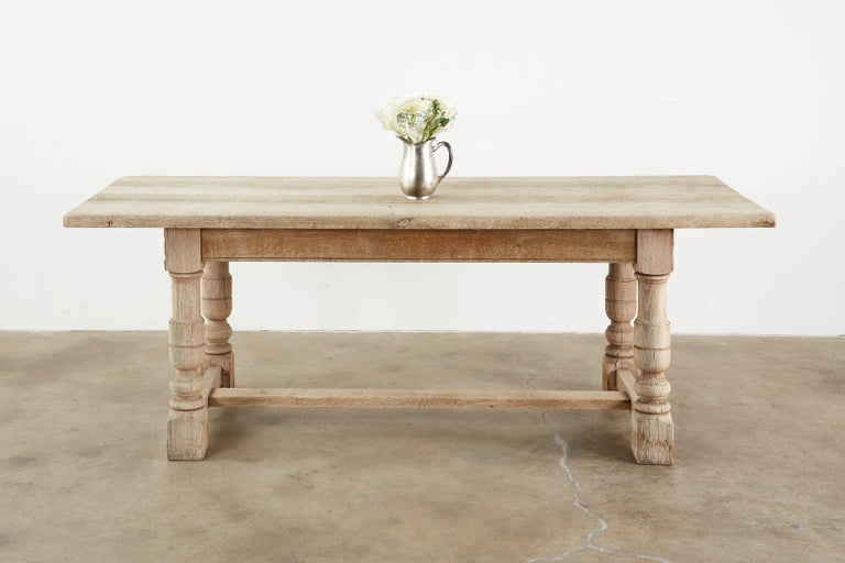 Rustic country French farmhouse dining table featuring a bleached oak distressed finish with an aged patina. Made in a grand trestle style with 1.5 inch thick plank top and thick, chunky turned legs ending with block feet. The legs are conjoined by