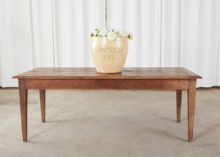 Rustic country French farmhouse harvest table or dining table crafted from pine and oak. The table features a framed plank top made of pine with an ogee edge. The base appears to be crafted from oak with wood peg joinery. Ample leg room measuring