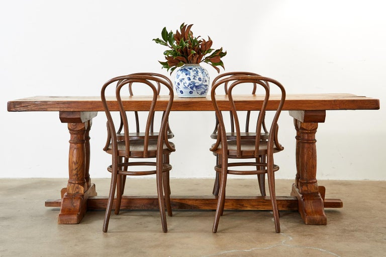 Rustic Country French farmhouse dining table featuring massive planks or reclaimed oak. The top measures 2.5 inches thick showcasing the antique wood grains and age. Supported by a massive trestle style base featuring thick column turned legs ending