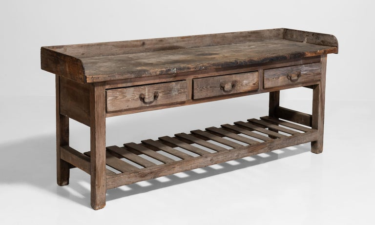 Country house prep table, England, circa 1849.  Three drawer pine work table with original iron handles and slatted shelf for storage.