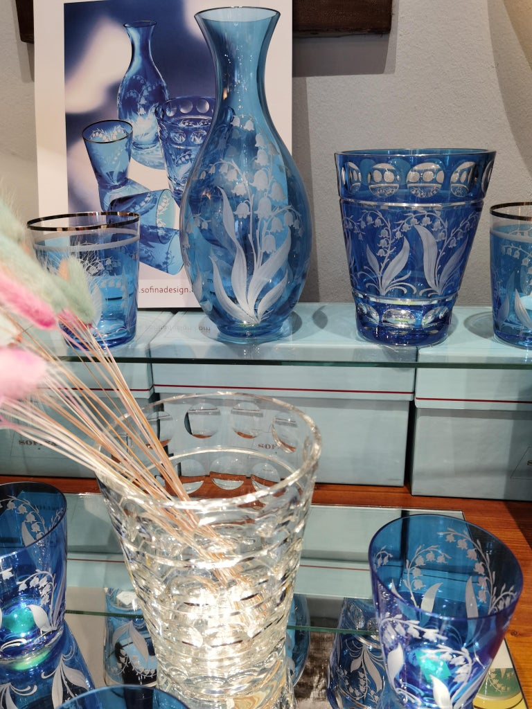 Hand blown crystal vase in light blue glass with lily of the valley decor all around. The blooms and leaves are hand-engraved by glass artists in Bavaria/Germany. The glass comes in a light blue color and can be ordered in different colors. Can be
