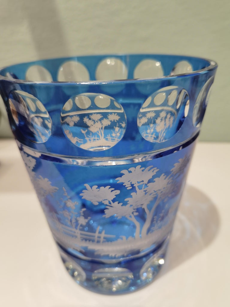 Hand blown crystal vase in blue glass with a country style decor all around. The leaves and deers are hand-engraved by glass artists in Bavaria/Germany. One side shows a bunny and the backside deers. The glass here shown comes in a blue color and