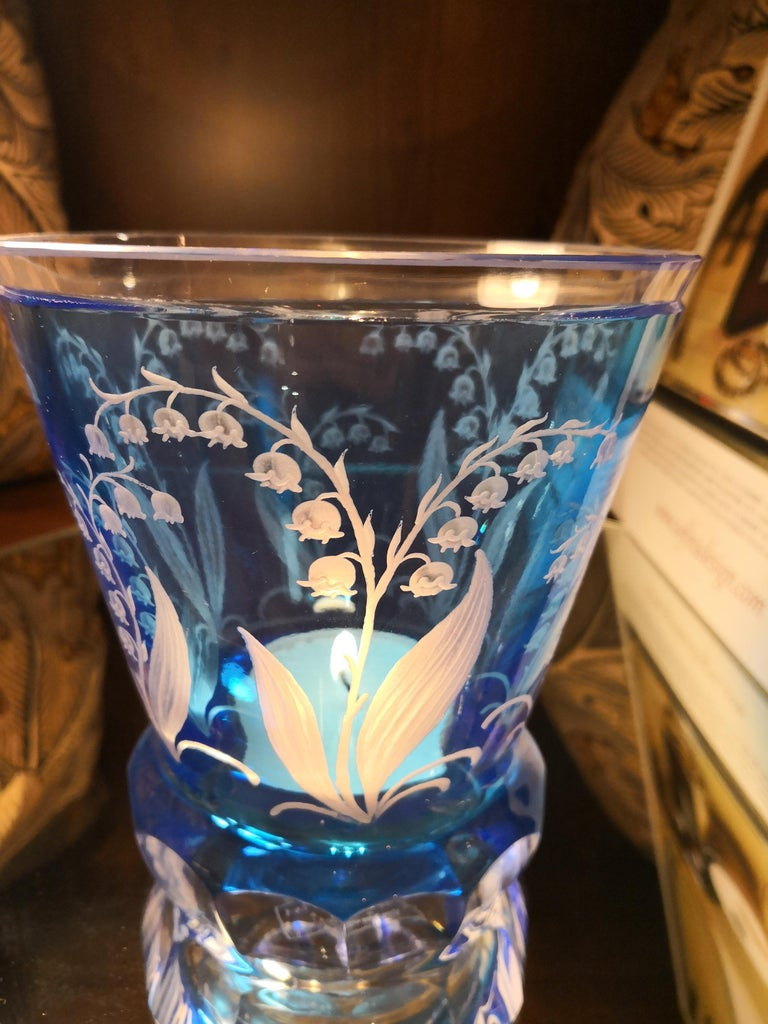 Hand blown crystal vase/latern in light blue glass with lily of the valley decor all around. The blooms and leaves are hand-engraved by glass artists in Bavaria/Germany. The glass comes in a light blue color and can be ordered in different colors.