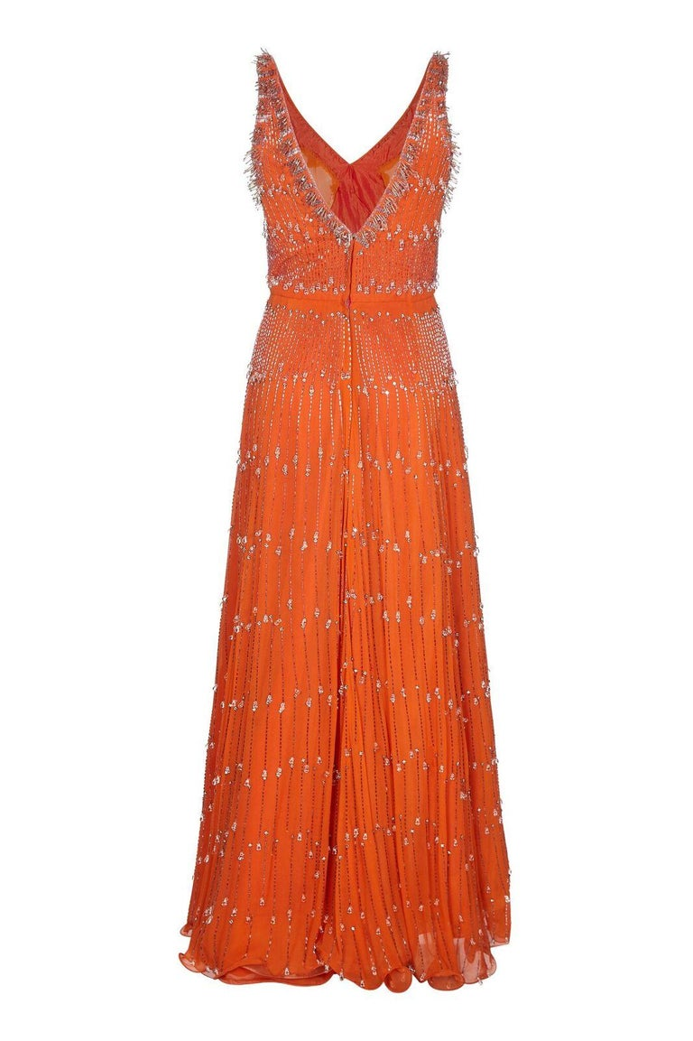 This magnificent late 1950s/ early 1960s silk chiffon beaded gown exudes haute couture quality. The burnt orange silk chiffon overlay showcases some fabulous crystal embellishment and beading that covers the gown in its entirety. Silver-toned bugle