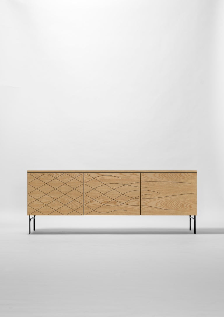 Sideboard in natural ash wood. Structure in anodic black lacquered steel. The doors carry black patterns made using the Wood TailoringTM technique.
