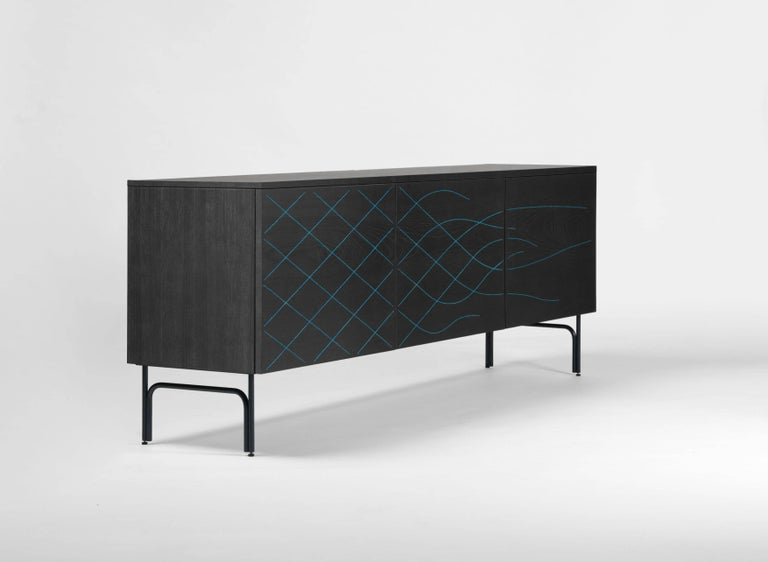 Sideboard in stained black ash. Structure in anodic black lacquered steel. Doors sewn in blue or orange thread.