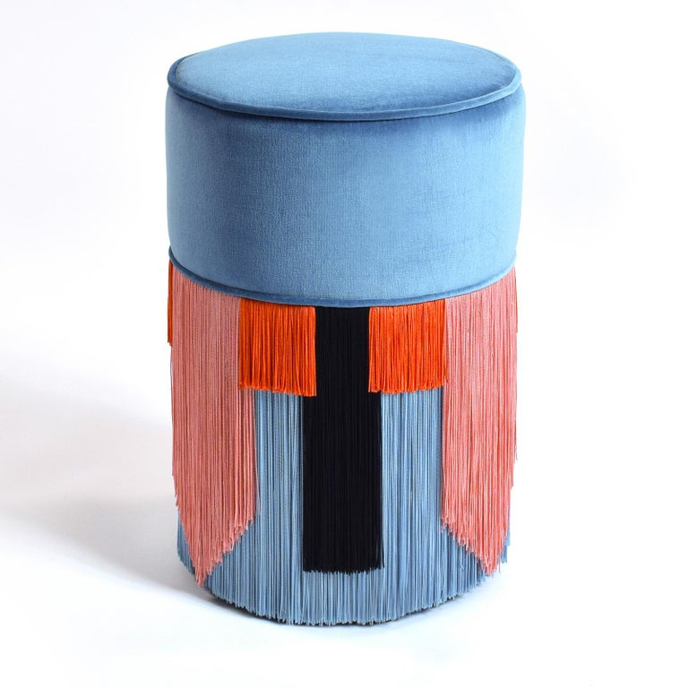 Marked by original design and vibrant colors, the tall and slender beech wood frame of this pouf supports the seat cushion, filled with synthetic padding and upholstered in a delicate light blue velvet for a long-lasting, soft feel. The bottom half