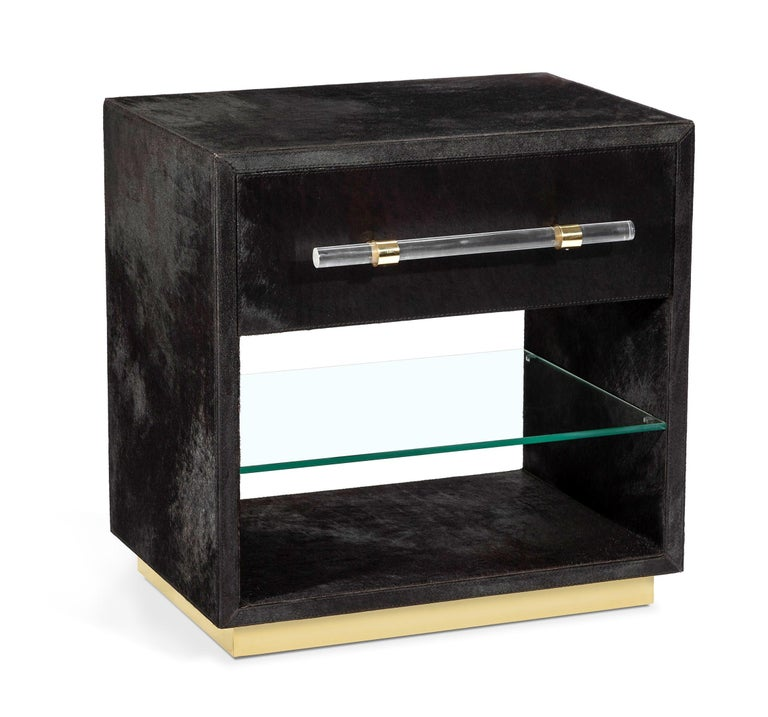 Handcrafted of natural black hide with a clear plexi glass handles and shiny brass detailing, the bedside tables will add a touch of style and sophistication to your bedroom. Hide is a natural material. Variations in coloration are to be expected