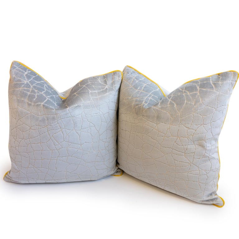 A hand sewn throw pillow made in a cut velvet fabric with