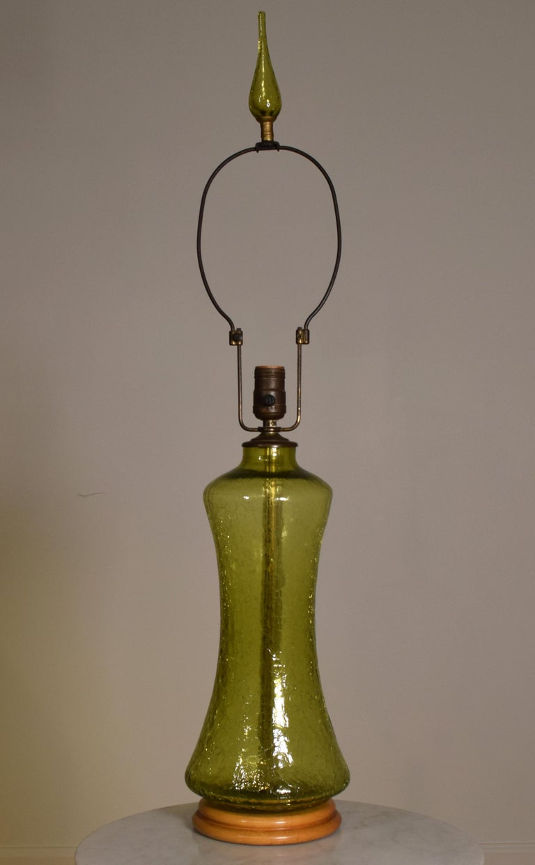 Model LP-14, A lovely single olive green art glass green table lamp by Blenko studio, 1970s. In a crackle finish on wood turned wood base with original adjustable harp with original finial. Perfect working condition, and can be re-wired with all new
