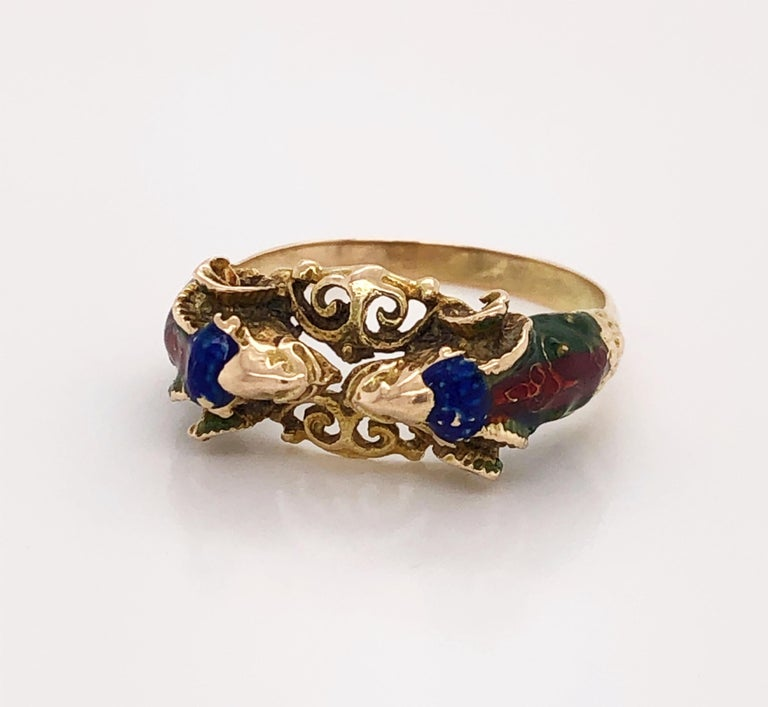 Two dueling rams create this interesting artisan ring in ten carat (10k) yellow gold. Bucking heads meet over center filigree and are hand painted with green, red and blue enamel accents. Unsigned. Band style in size 8-1/2 . in gift box.