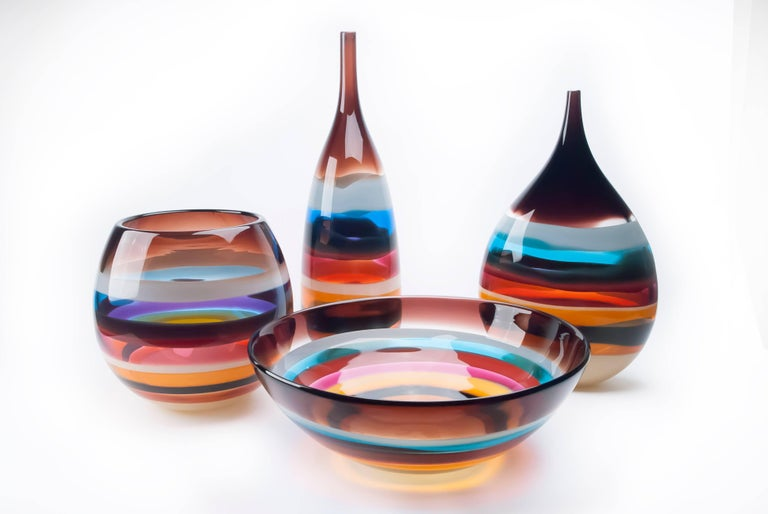 These striking pieces draw inspiration from the rich hues and undulating topography of Southern California. Alternating layers of opaque and transparent colors are applied to clear glass. Overlaps create opportunities for new colors to be formed,