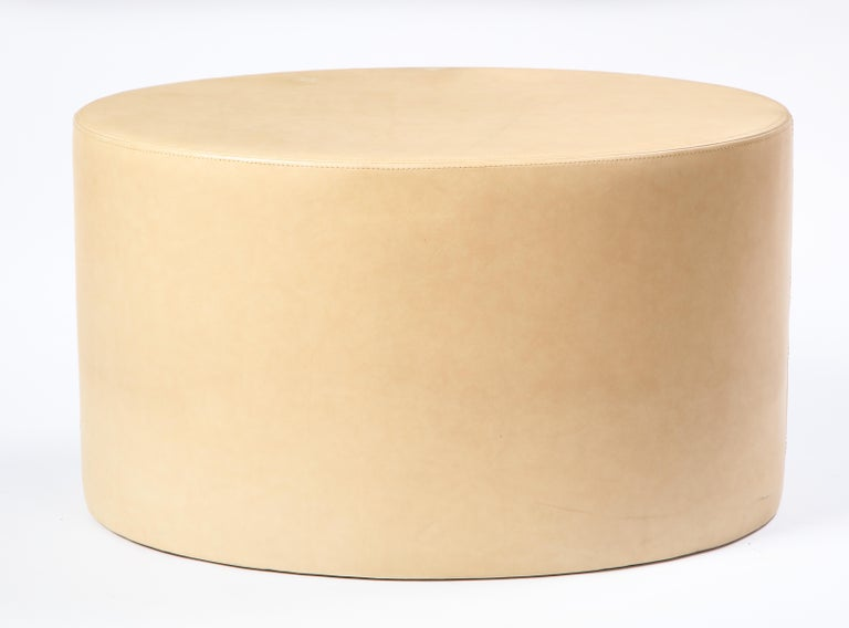 Modern cream-colored leather low table or ottoman. Oval in shape, this topstitched leather-covered low table adds a warm touch to any modern seating arrangement and is perfect as a side or coffee table for any living room or lounge area.  Property