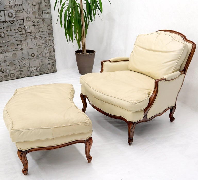 French country 2-part chaise lounge and ottoman. Hi grade supple cream leather upholstery. Beautiful carved walnut frame. Super comfortable elegant looking down filled cushions piece of furniture. Measures: Overall length 63