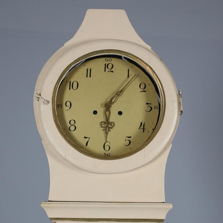 Antique Swedish country Mora clock from early 1800s in probable original cream paint finish with a great delicate shape body and a good face with lots of detail and nicely detailed hood in good condition.   It has the Classic extended belly of a