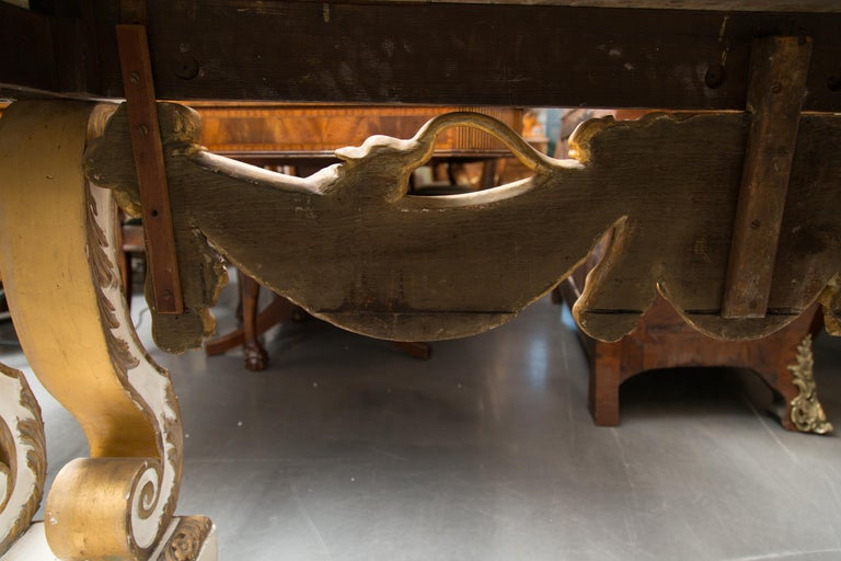 This is an impressive and large-scale cream-painted and parcel gilt console table. The rouge variegated marble top is above a central ornamentation of a lion mask flanked by bold drapery-form swags. The entirety of the console is supported by a