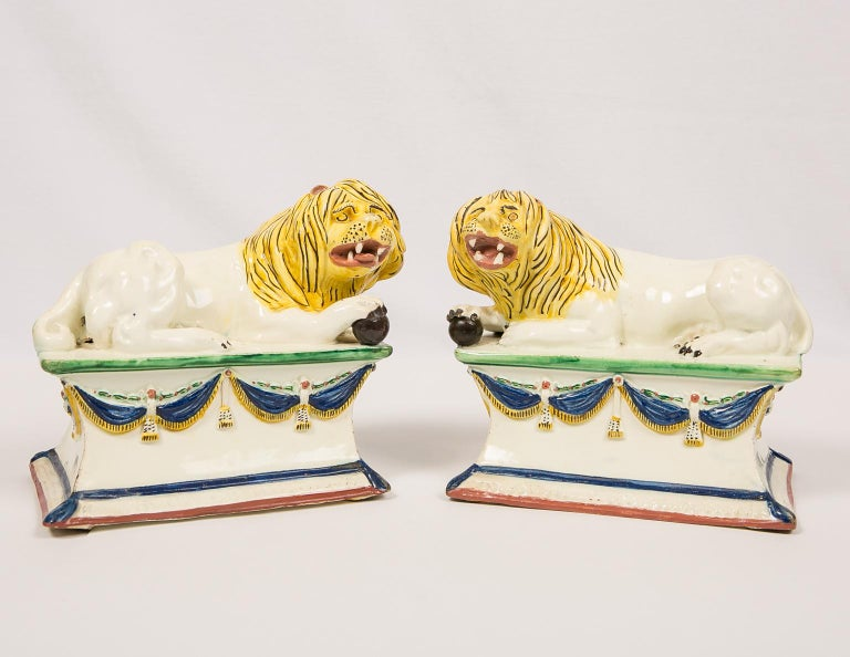 A fine and rare pair of creamware lions each resting on a tall base decorated with swags of dark blue