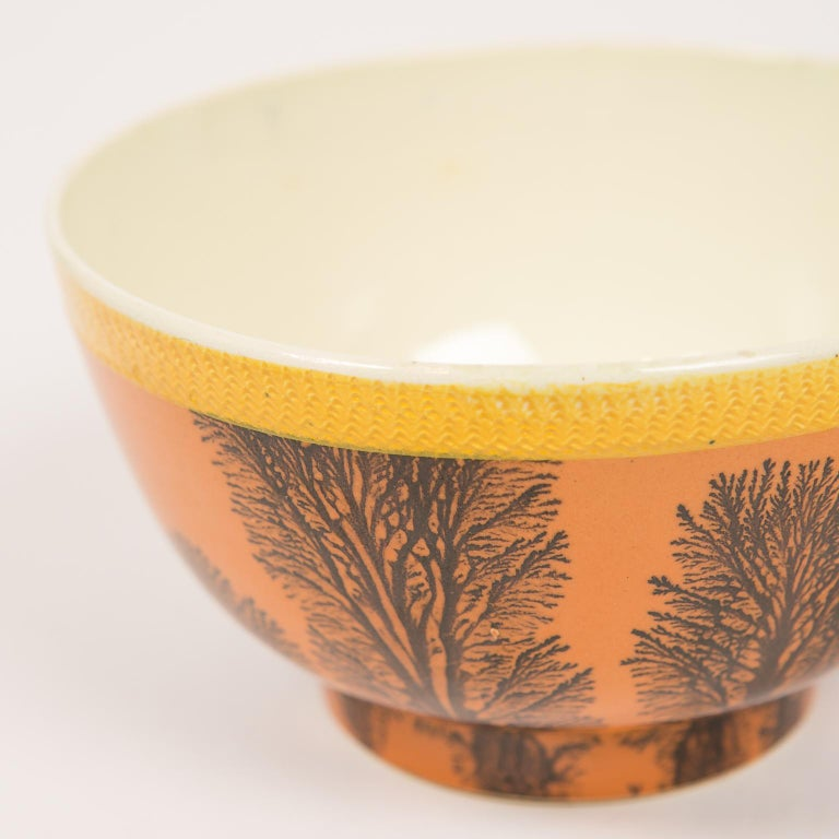 WHY WE LOVE IT: We love all mochaware. This is in a class by itself! This beautiful and rare creamware mochaware bowl has a thin yellow band of impressed decoration around the top edge, below that is a broad band of orange slip which is decorated