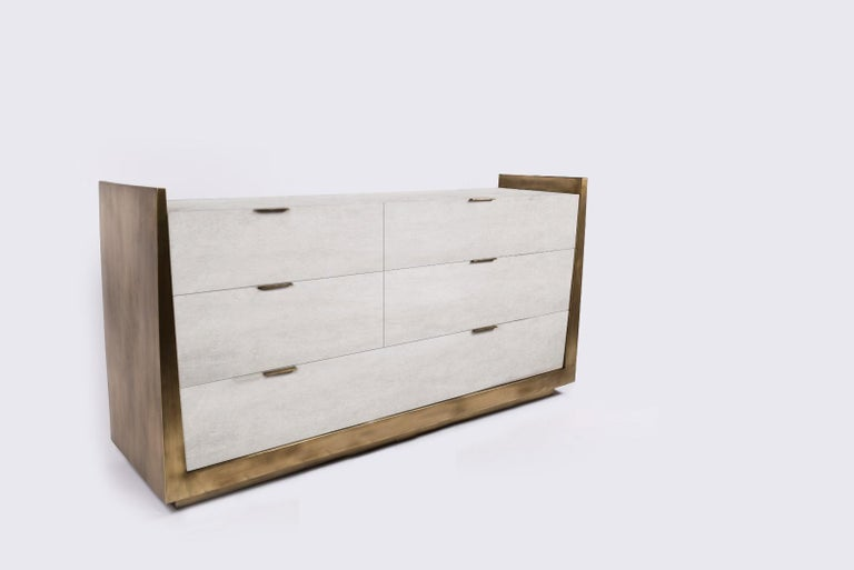 The Lola Credenza by R&Y Augousti is an elegant piece with its subtle geometry. This case storage is inlaid in cream parchment, with the sides completely inlaid in bronze-patina brass. The piece is finished off with discreet bronze-patina brass flat