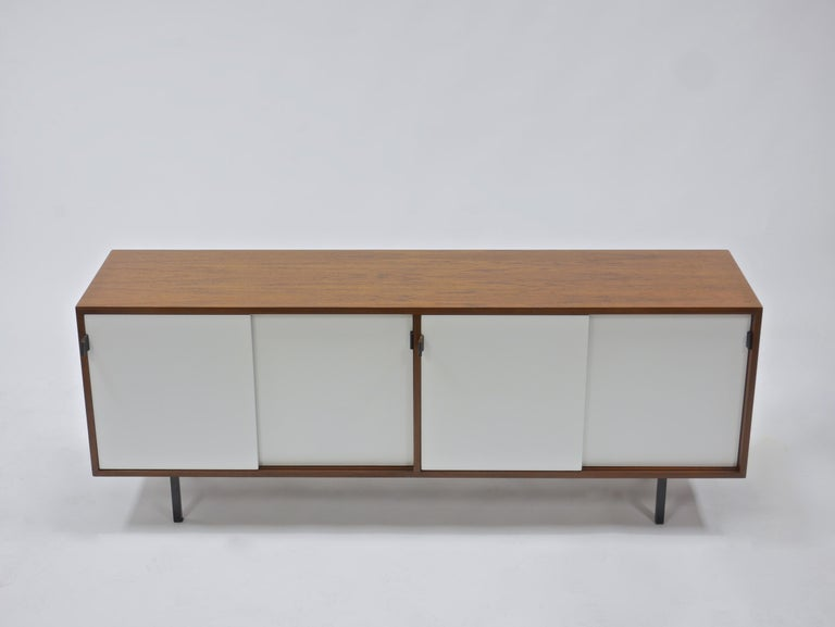 Credenza in walnut and white lacquer by Florence Knoll. Having leather pulls, steel legs and four oak lined compartments, each with a shelf. A handsome example with highly figured walnut veneers. Knoll Associates label. See our other listings for a