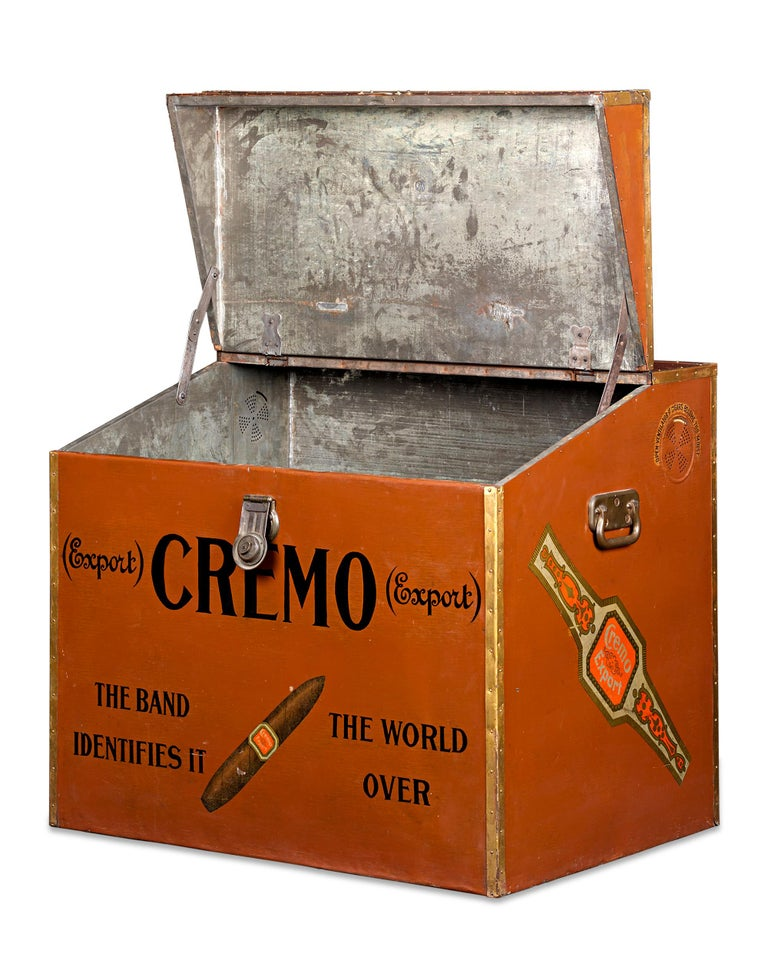 This monumental humidor trunk was made by Cremo Cigars to house and advertise the company's famed cigars in tobacco shops. The trunk remains in fantastic condition, featuring a polychrome exterior and Cremo's logo and famed slogan
