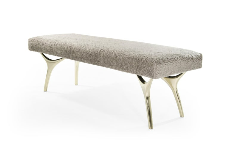 The Crescent Bench  Articulate, sharp and functional. One of Stamford Modern's most sought after designs. Sculptural handcrafted and polished solid brass legs in a satin finish. Shown upholstered in 100% longhair mohair by Holly Hunt. Fabric